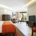Innenansicht mit Doppelbett, Couch und großem Flachbildschirm in einer Junior Suite im 6-Sterne Hotel Royal Palm Beachcomber auf Mauritius.