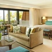 Innenansicht einer Tropical Suite mit Balkon und Blick auf das Meer im 6-Sterne Hotel Royal Palm Beachcomber Luxury auf Mauritius.