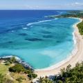 Luftaufnahme auf die Bucht mit weißem Sandstrand und kristallkarem Wasser vor dem 5-Sterne Hotel Shandrani Beachcomber auf Mauritius.