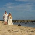Brautpaar geht am Strand von Mauritius spazieren. Braut traegt Brautstrauss und weissen Hut.