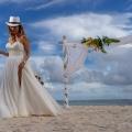 Braut mit Sektglas und weissem Hut mit Traubogen am Strand von Mauritius.