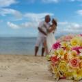 Strand auf Mauritius mit Brautpaar im Hintergrund und Brautstrauss im Vordergrund.
