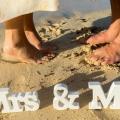Fueße eines Brautpaars im Sand mit Mrs und Mr Holzbuchstaben.