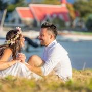 Lachendes Brautpaar sitzt vor der Kirche am Cap Malheureux auf Mauritius.