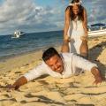 Froehliches Brautpaar auf Mauritius. Braut zieht Bräutigam an den Beinen über den Sand.