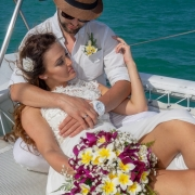 Verliebtes Paar liegt entspannt mit Brautkleid im Netz des Katamarans auf Mauritius.