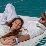 Verliebtes Paar liegt entspannt mit Brautkleid im Netz des Katamarans in Mauritius.