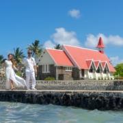 Brautpaar vor der roten Kirche am Cap Malheureux auf Mauritius auf dem Weg zur Trauung auf dem Katamaran.