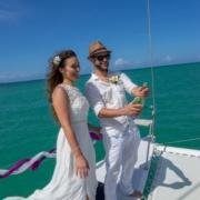 Verliebtes Brautpaar öffnet Champagnerflasche auf dem Katamaran in Mauritus.