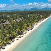 Luftaufnahme des 5-Sterne Hotel Trou aux Biches Mauritius Beachcomber. Langer, weißer Sandstrand mit Palmen und Sonnenschirmen.