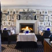Das Restaurant Azure, Tisch für 2 Personen am brennenden Kamin im 4-Sterne Hotel Twelve Apostel in Suedafrika.