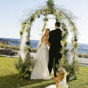 Brautpaar mit Blumenmaedchen unter geschmuecktem Hochzeitspavillion im Fynbos Garden. Heiraten im 4-Sterne Hotel Twelve Apostel in Suedafrika.