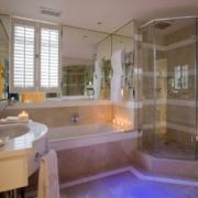 Badezimmer mit Dusche und Badewanne im Luxury Room im 4-Sterne Hotel Twelve Apostel in Suedafrika.