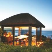 Spa im 4-Sterne Hotels Twelve Apostel in Suedafrika mit verglastem Gazebo mit Blick ueber die Bucht am Abend.