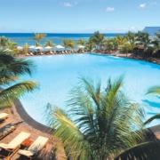 Grosser Pool mit Liegen und Palmen und Blick auf das Meer im 4-Sterne Victoria Beachcomber Resort und Spa.