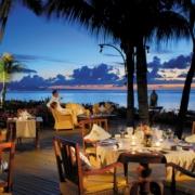 Paar sitzt am Abend auf der Restaurantterrasse im 4-Sterne Victoria Beachcomber Resort und Spa und geniesst den Sonnenuntergang.