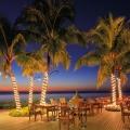 Die Terrasse des Restaurants im 4-Sterne Victoria Beachcomber Resort & Spa auf Mauritius bei Sonnenuntergant. Gedeckte Tische und Palmen mit Lichterketten um den Stamm.