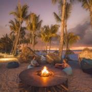 Lagerfeuer am Strand des 4-Sterne adult-only Hotel Victoria For2 auf Mauritius. Junges Paar geniesst die Abendstimmung am Feuer.