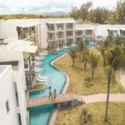 Luftaufnahme eines jungen Paars, das ueber die Bruecke ueber den Pool im 4-Sterne adult-only Hotel Victoria For2 auf Mauritius geht.