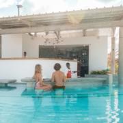 Bar im Pool im 4-Sterne adult-only Hotel Victoria For 2 auf Mauritius.. Junges Paar sitzt an der Bar im Wasser und wird von lachendem Kellner bedient.