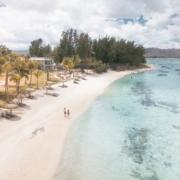Luftaufnahme von jungem Paar das am weissen Sandstrand im im 4-Sterne adult-only Hotel Victoria For 2 auf Mauritius spazieren geht.
