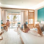 Junges Paar im Zimmer im 4-Sterne adult-only Hotel Victoria For 2 auf Mauritius. Junge Frau liegt auf dem Bett mit Blick auf den Strand, der junge Mann sitzt mit Laptop am Schreibtisch.
