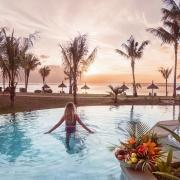 Junge Frau bei Sonnenuntergang im Pool des 4-Sterne adult-only Hotel Victoria For2 auf Mauritius.