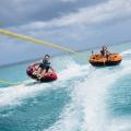 Zwei junge Mönner im Schwimmreifeh werden vom Boot gezogen in Barbados vor dem 4-Sterne Plus Hotel The Waves Hotel & Spa.