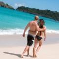 Verliebtes Paar geht Arm in Arm am Strand des 4-Sterne Galley Bay Resort und Spa auf Antigua entlang.