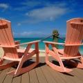 Rosa Schaukelstuehle auf Sonnendeck im 4-Sterne Galley Bay Resort und Spa auf Antigua.
