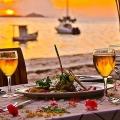 Gedeckter Tisch mit Wein und Essen im Sonnenuntergang im 3-Sterne Plus Hotel Indian Ocean Lodge auf der Insel Praslin, Seychellen.