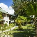 Der Garten mit Wohngebaeuden im 3-Sterne Plus Hotel Indian Ocean Lodge auf der Insel Praslin, Seychellen.