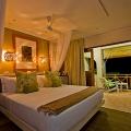 Zimmer mit Doppelbett und Balkon in 3-Sterne Plus Hotel Indian Ocean Lodge auf der Insel Praslin, Seychellen.