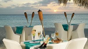 Romantisch gedeckte Tische am Strand im Sonnenuntergang im 4-Sterne Hotel Amsterdam Manor Beach Resort in Aruba.