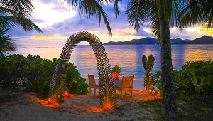 Geschmueckter Tisch am Strand mit Bogen aus Palmblaettern zum Honeymooner Abendessen im 3-Sterne plus Hotel La Digue Island Lodge auf den Seychellen.