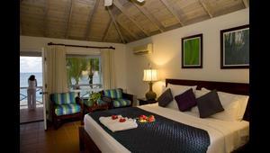Doppelbett und Sessel in einem DeLuxe Zimmer im 4-Sterne Hotel Blue Haven auf Tobago.