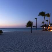 Pavillions direkt am Strand am Abend mit romantischer Beleuchtung im 4-Sterne Plus Hotel Bucuti & Tara Beach Resort.