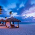 Einzelne Pavillions mit Tischen am Strand im 4-Sterne Plus Hotel Bucuti & Tara Beach Resort bei Sonnenutergang.