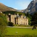 Hochzeitshotel 5-Sterne Hotel Fort Willilam - Inverlochy Castle in Schottland. Blick auf das Castle im Hintergrund die Berge im Vordergrund eine Wiese mit Schafen.