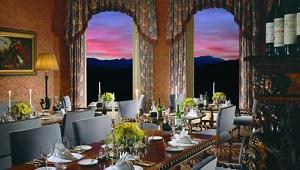 Das Restaurant im 5-Sterne Hotel Inverlochy Castle in Fort William/Schottland. Im Hintergrund ist der Sonnenuntergang zu sehen, die Tische sind stilvoll mit Kerzen gedeckt.