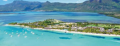 Luftaufnahme auf eine Bucht in Mauritius mit Booten um Wasser und Bergen im Hintergrund