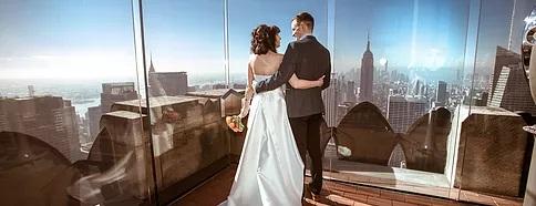 Brautpaar auf dem Rockefeller Center in New York direkt nach der Trauung. Im Hintergrund die Skyline von New York.