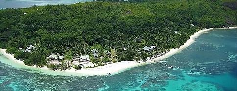 Luftaufnahme auf einen Strand auf den Seychellen mit einsamem, weissem Sand und tuerkiesfarbenem Wasser