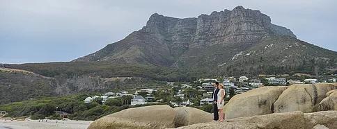 Brautpaar auf einem Felsen vor dem Tafelberg in Kapstadt.