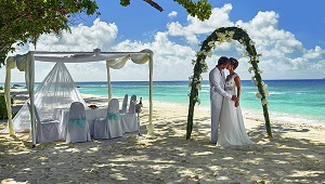 Kuessendes Brautpaar unter Traubogen und geschmücktem Pavillion am Strand des 5-Sterne Hilton Seychelles Labriz Resort & Spa auf der Privatinsel Silhouette Island.