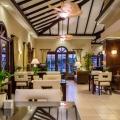Loungebereich im 4-Sterne Plus Hotel Bucuti & Tara Beach Resort. Zweiertische mit weissen Stuehlen, im Hintergrund ein Fruehstuecksbuffet.