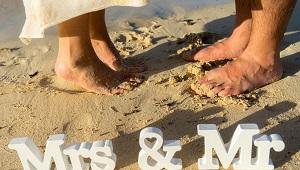 Fuesse eines Brautpaars im Sand mit Mrs und Mr Holzbuchstaben.