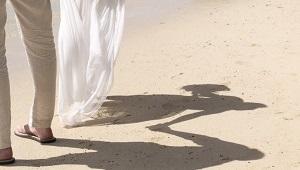 Brautpaar am Strand haelt sich bei der Hand. Man kann nur den Schatten der beiden im Sand sehen und ihre Beine.