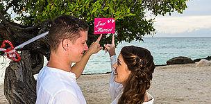 Brautpaar an einem Baum in Aruba das auf ein Frisch verheiratet Schild zeigt.