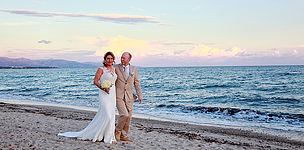 Brautpaar geht an einem Strand auf Sardinien im Sonnenuntergang spazieren.